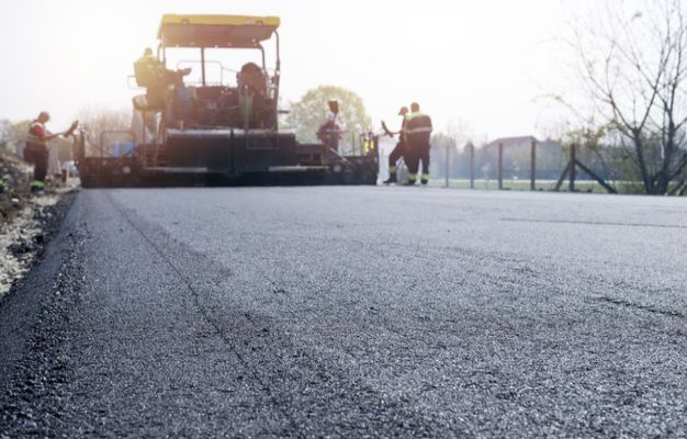 workers-placing-new-coating-asphalt-road_342744-601